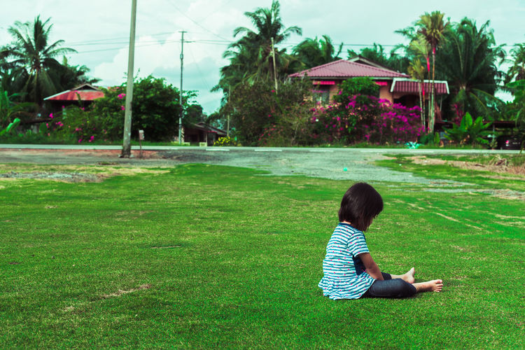 Rear view of woman sitting on grass