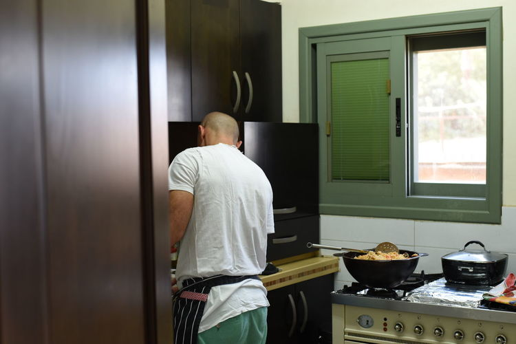 Rear view of man cooking in kitchen