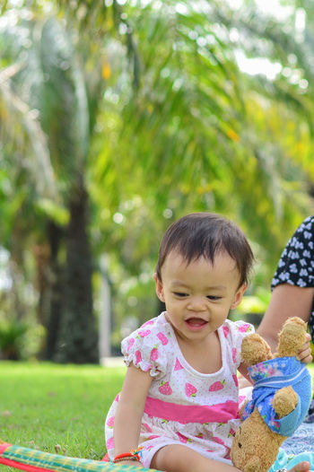Asian baby girl playing in park. Child Childhood Innocence Real People Girls Cute Women Day Females Focus On Foreground People Plant Lifestyles Leisure Activity Looking Baby Three Quarter Length Two People Front View Sitting Outdoors