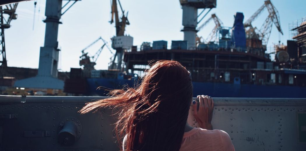 Rear view of woman against ship