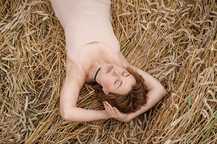 High angle view of woman lying on field