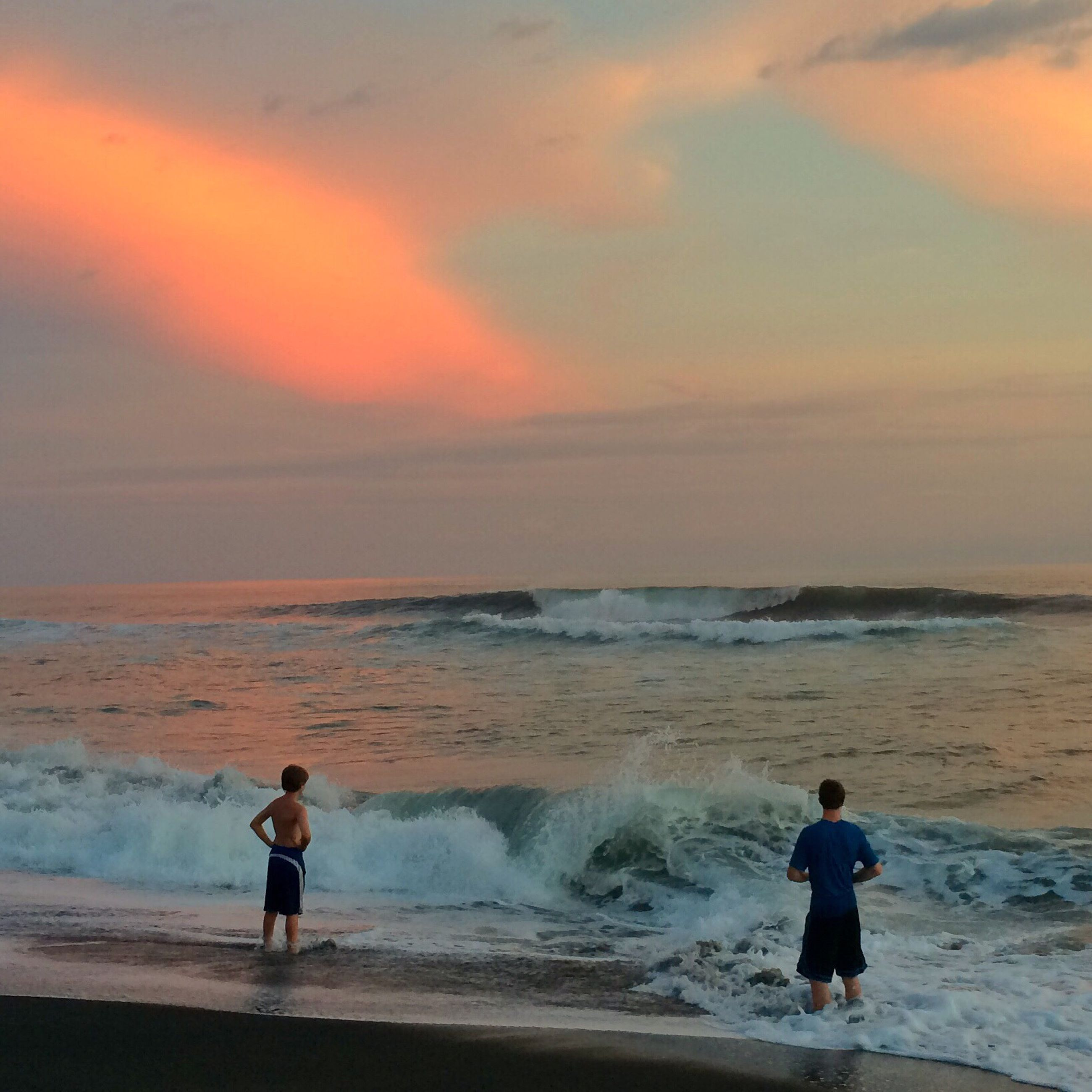 water, sea, beach, full length, lifestyles, leisure activity, shore, horizon over water, standing, rear view, sky, childhood, beauty in nature, scenics, vacations, sunset, casual clothing, boys