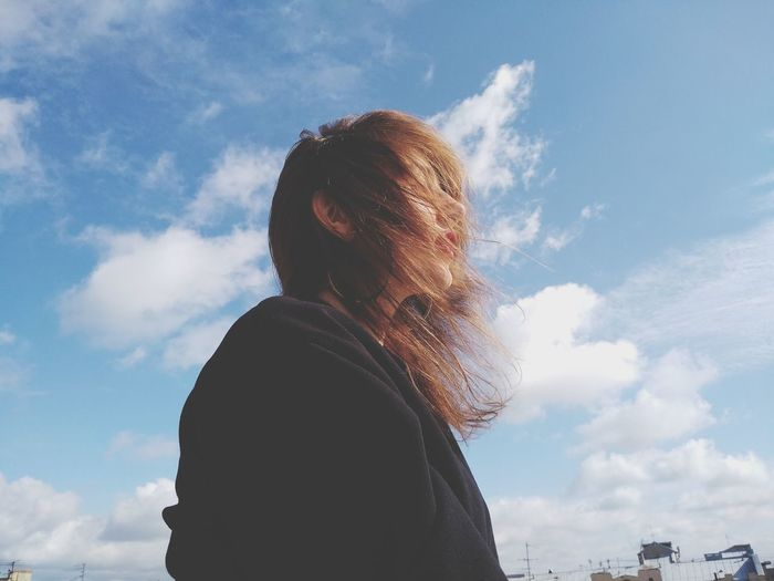 Portrait of woman looking at camera against sky
