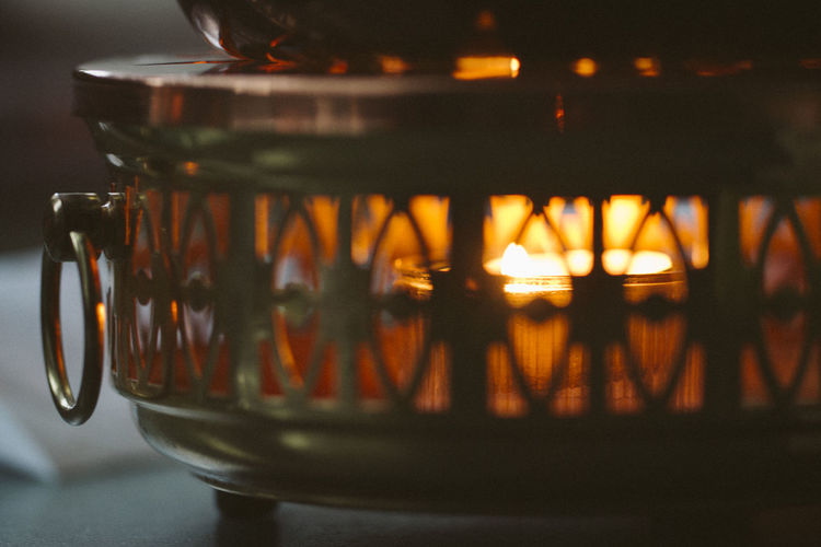 Illuminated Candle In Metallic Lantern On Table