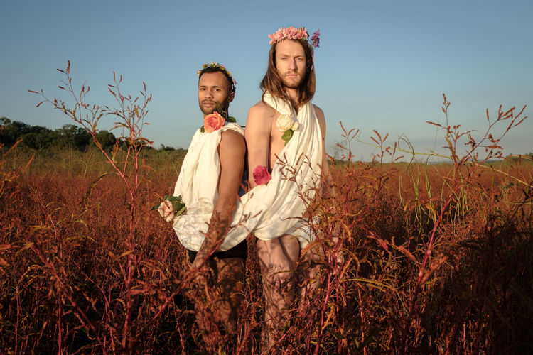 Portrait of gay men wearing flowers standing amidst plants against clear sky