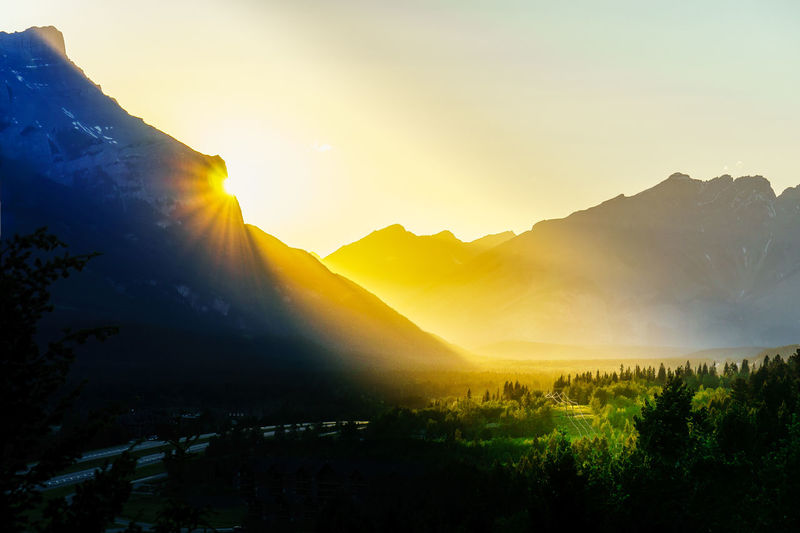 Sun setting on Mt. Rundle and Canmore Alberta. Alberta Banff National Park  Beauty In Nature Day Dramatic Landscape Dramatic Sky Landscape Mountain Mountain Range Nature No People Outdoors Scenics Sky Sunlight Sunset Tranquil Scene Tranquility Tree