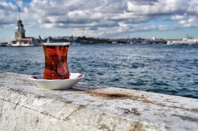 Close-Up Of Turkish Tea By Sea Against Cloudy Sky