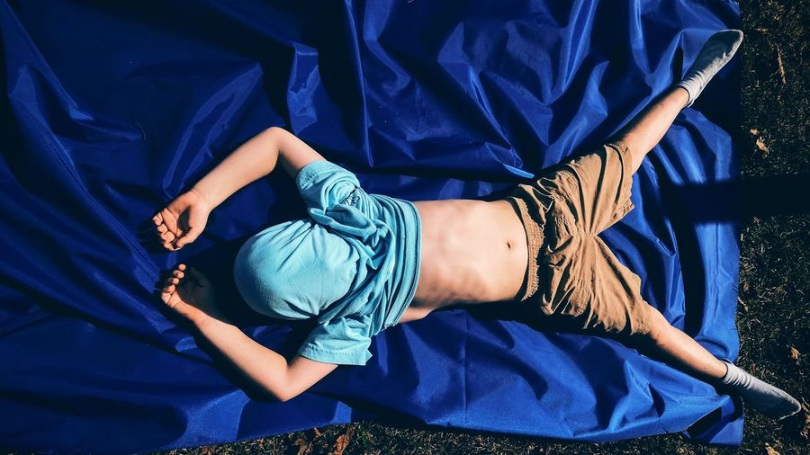 Full length of boy with covered face sleeping on blue fabric in yard