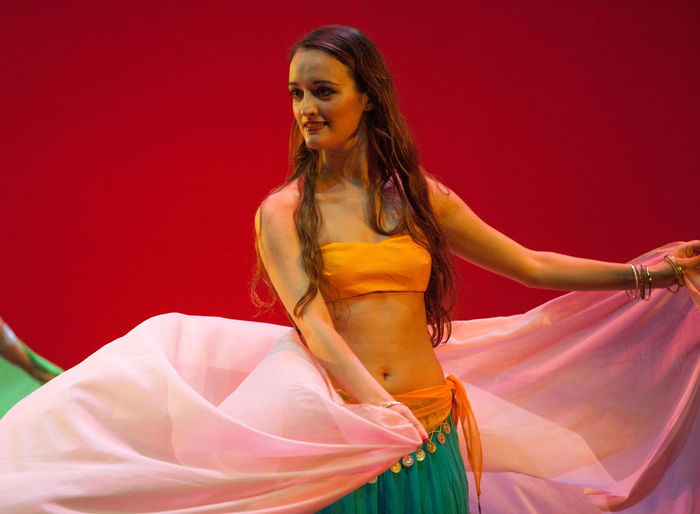 Smiling Woman Belly Dancing Against Red Background