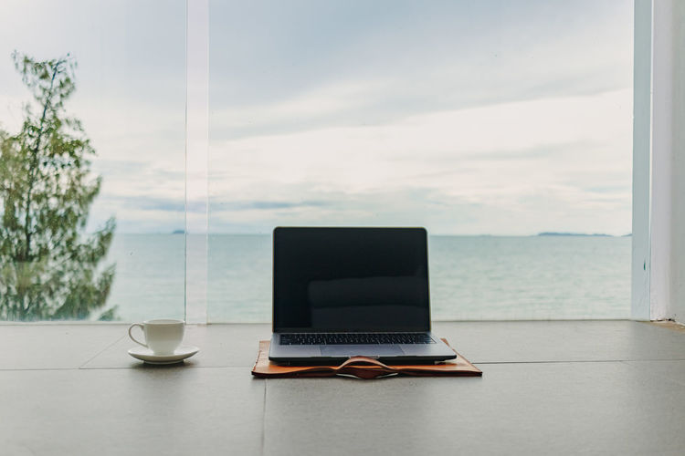 Coffee cup on table against window