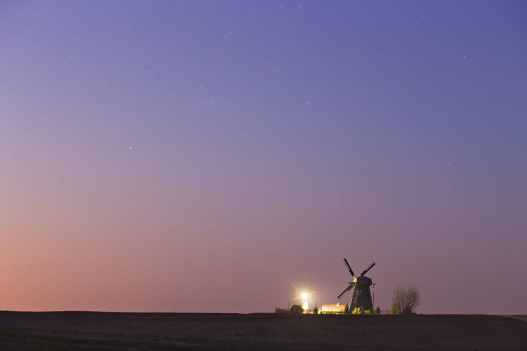 Windmills against sky at night