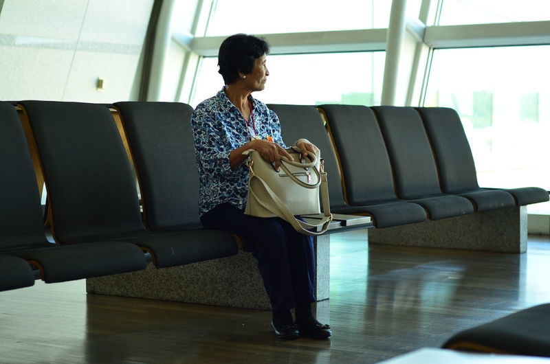 A lady waiting at the airport terminal Adult Airport Terminal Casual Clothing Communication Connection Flooring Full Length Furniture Hairstyle Holding Home Interior Indoors  Leisure Activity Lifestyles One Person Real People Sitting Sofa Technology Wireless Technology Women