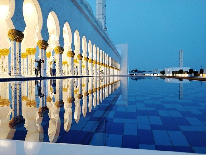 Reflection of buildings in swimming pool against clear sky