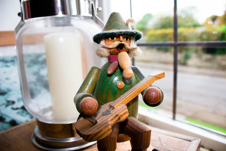 Close-Up Of Wooden Figurine By Lantern Against Window