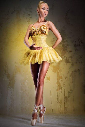 Beautiful ballerina dancing against yellow background