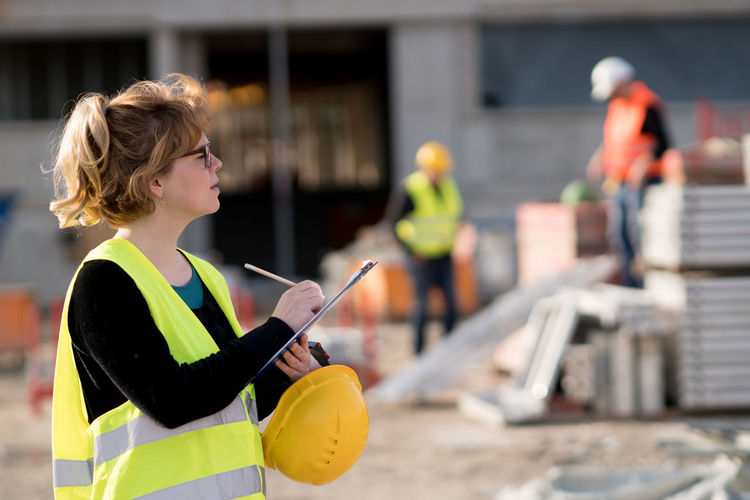 Side View Of Female Architect Working At Construction Site