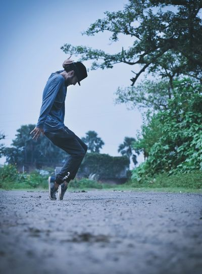Side view of man jumping against trees