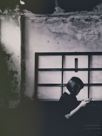 Side view of woman standing against window in abandoned building