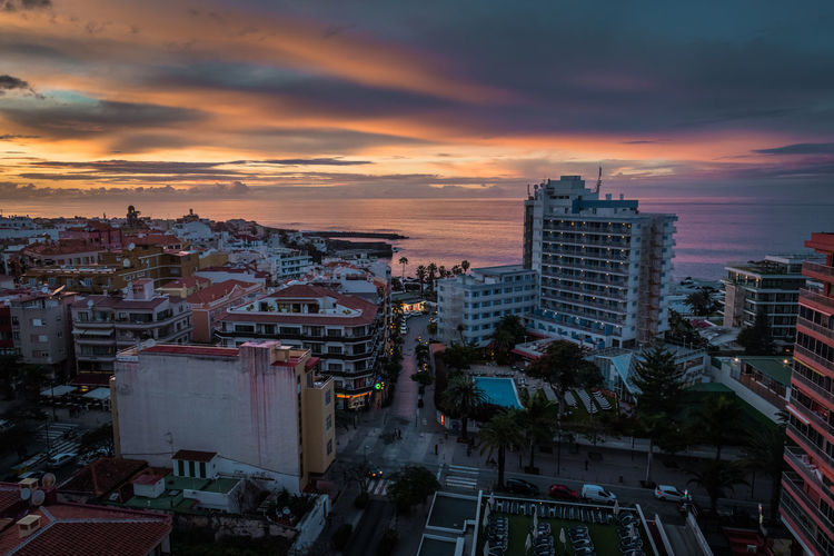 PUERTO DE LA CRUZ, TENERIFE / SPAIN - FEBRUARY 24 2018: View from the Architecture Building Building Exterior Built Structure City Cityscape Cloud - Sky Dramatic Sky High Angle View Nature No People Office Building Exterior Orange Color Outdoors Residential District Romantic Sky Sky Skyscraper Sunset Tree
