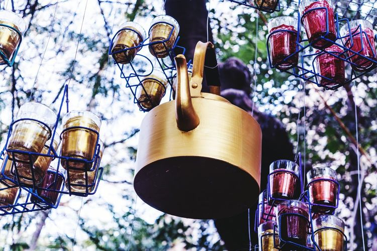 Low Angle View Of Artwork Made From Teapot And Glasses Hanging To Tree