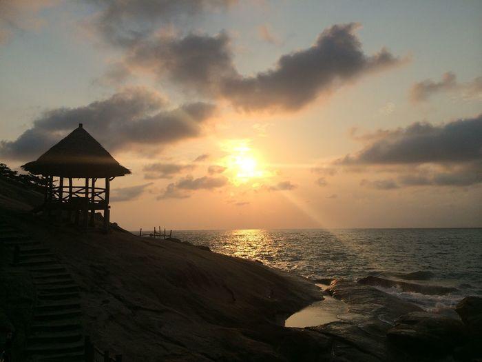 Gazebo on beach against sky during sunrise