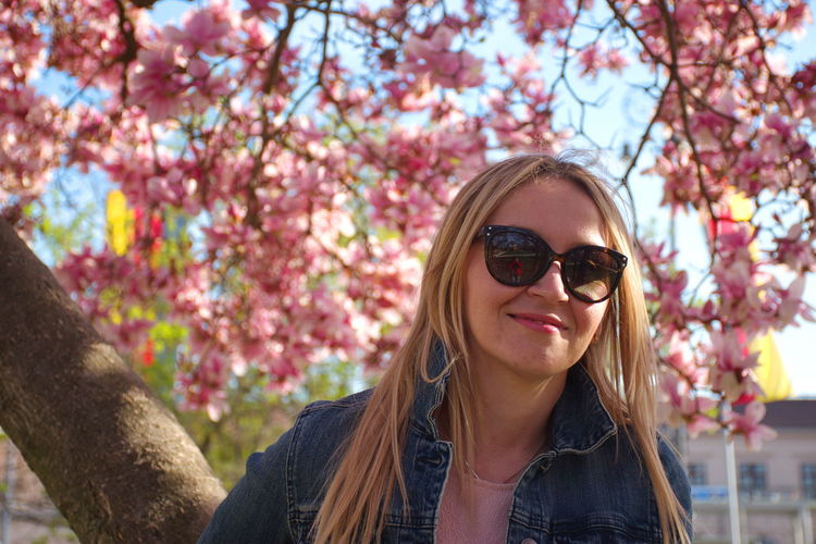 One Person Lifestyles Leisure Activity Real People Long Hair Tree Front View Hair Young Adult Portrait Young Women Plant Hairstyle Day Focus On Foreground Blond Hair Nature Women Outdoors Beautiful Woman Sunglasses Magnolia Blooming Flowers Park Springtime Jeans Fashion Pink Color