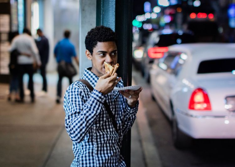 Young man eating food on sidewalk at night