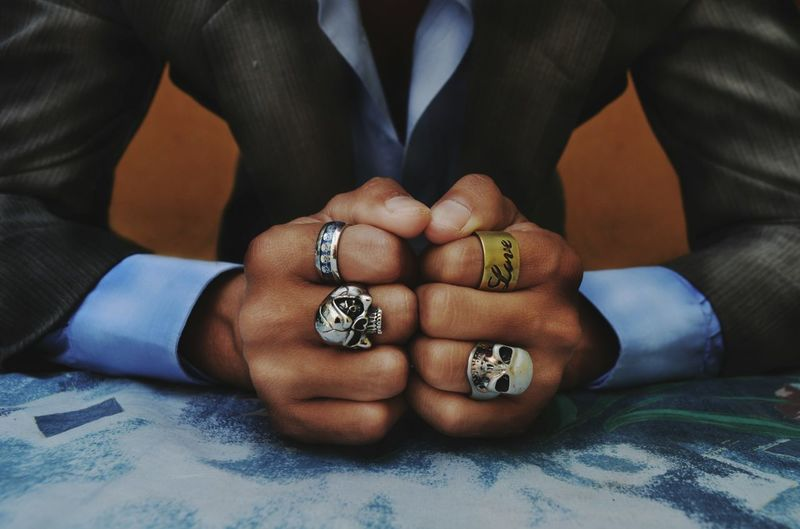 Midsection Of Man Wearing Rings At Table