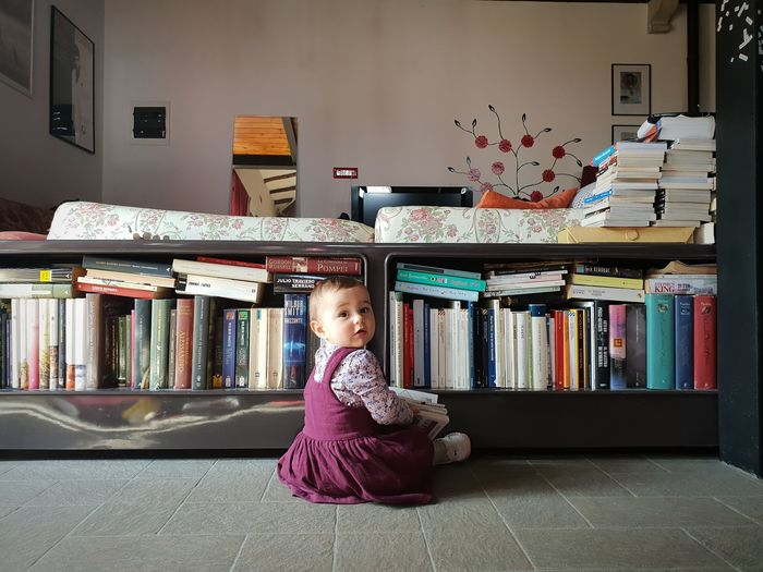 Boy sitting on book at home