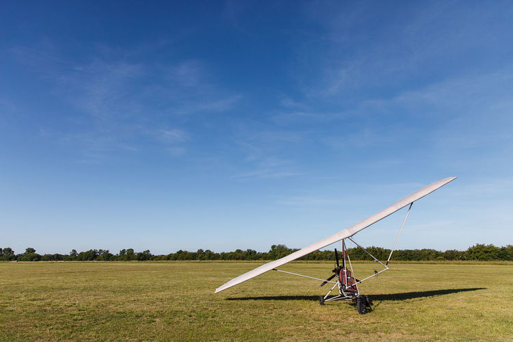 Powered hang glider on field against sky
