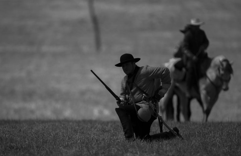 A Confederate Cavalry soldier re-loads his musket during a cavalry demonstration and civil war re-enactment on the 157th Anniversary of the Battle of Shiloh in Shiloh, Tennessee. The Confederate soldiers often had to bring their own horses and saddles to battle while the Union army were furnished with both. Domestic Animals Domestic Mammal Animal Wildlife Field Land Pets Vertebrate Livestock Horseback Riding Real People People One Animal Men Nature Horse Day Hunter Outdoors Herbivorous Riding Civil War Civil War History Civil War Re-enactments Battle Battle Of Shiloh Photojournalism Silhouette Cavalry Cavalry Soldier Cavalryman Cavalry Charge Cavalry Battle