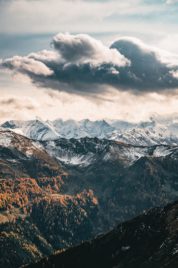 Dramatic sky over snow capped mountains in fall colors, saalbach, salzburg, austria