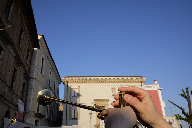 Cropped Hands Of Man Playing Trumpet Against Clear Blue Sky