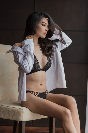 Seductive woman wearing lingerie and unbuttoned shirt sitting at home