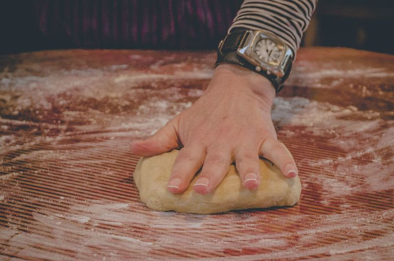 Close-up of hand kneading dough on counter
