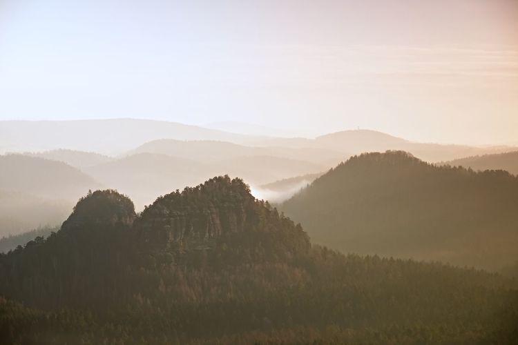 Sunrise in a beautiful mountain of czech-saxony switzerland. sandstone peaks increased from fog
