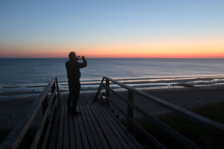 Man standing on railing by sea against sky during sunset