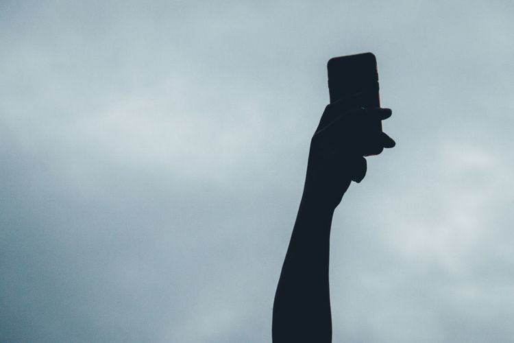 Low angle view of silhouette hand holding phone against cloudy sky