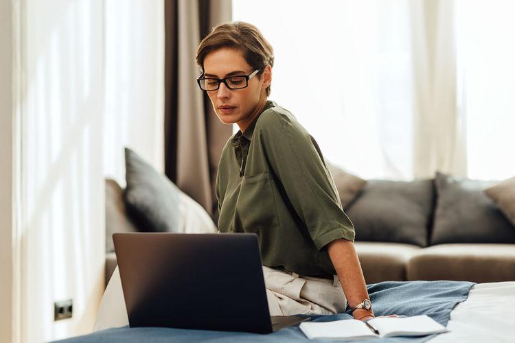 Beautiful woman using laptop sitting at home