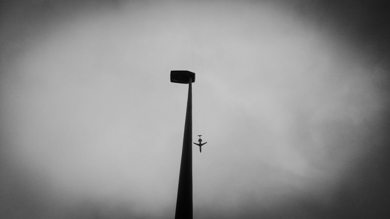 Street Light Against Overcast Sky With Airplane In Distance