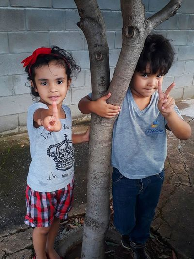 Portrait of girl with brother gesturing