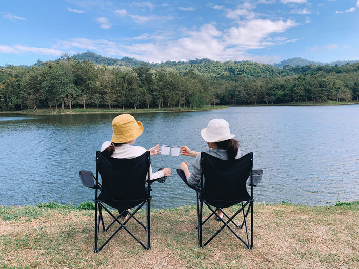 Rear view of men sitting by lake against sky
