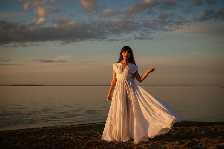 Beautiful young woman in a white long dress near the sea at sunset stands