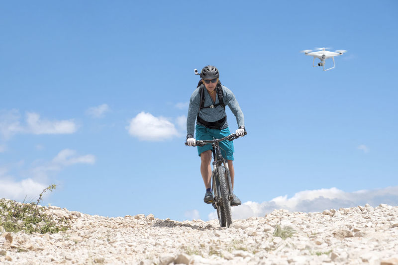 Mountain biker with helmet camera rides a bright gravel road and is followed by a white drone Camera Drone  Mountain Bike Rider Road Action Shot  Bicycle Blue Cycling Cycling Helmet Day Gravel Helmet Cam Leisure Activity Lifestyles Mountain Bike One Person Outdoors Person Riding Sky Sport Transportation