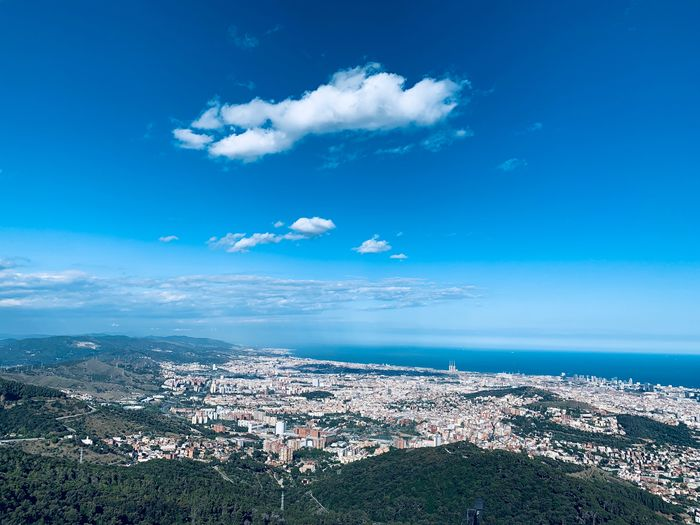 High angle view of city by sea against blue sky