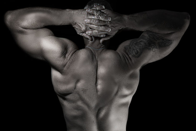 Close-Up Of Shirtless Man Flexing Muscles Against Black Background