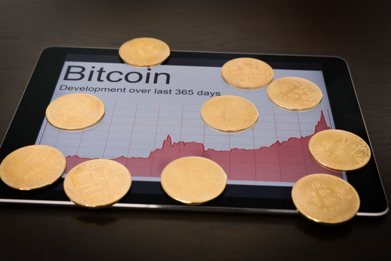 Blockchain concept : Rise of Bitcoin price. Digital tablet showing increasing price graph with coins of the cryptocurrency. Bitcoin Blockchain Chart Coins Cryptocurrency Digital Tablet Success