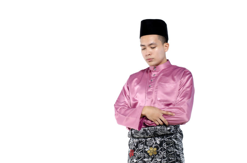 Portrait of young and handsome asian man with traditional clothing during hari raya over white background Studio Shot White Background One Person Standing Indoors  Front View Copy Space Three Quarter Length Young Adult Clothing Cut Out Casual Clothing Waist Up Young Men Lifestyles Looking Looking Away Confidence  Menswear