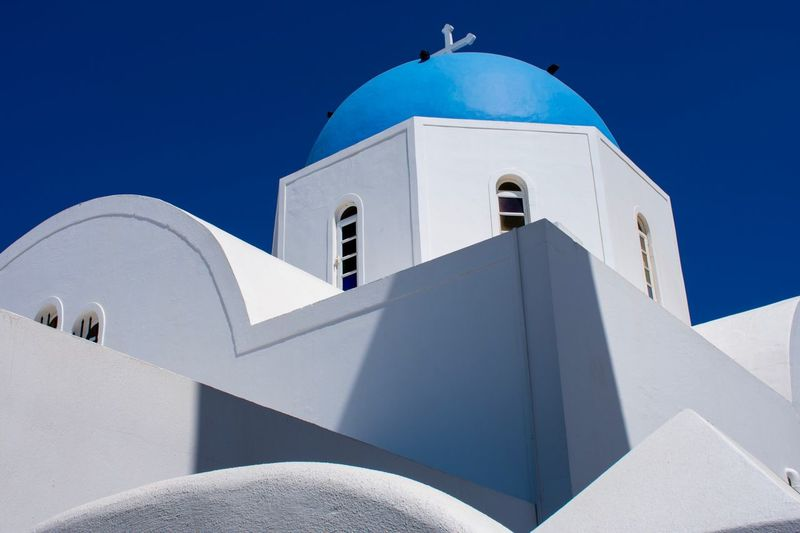 Christian church in Santorini Christianity Summer Imerovigli Santorini EyEmNewHere Imerovigli EyeEm Selects Built Structure Architecture Building Exterior Place Of Worship Spirituality Belief Religion Sunlight Building Blue Nature Dome Clear Sky No People Day Sky Tower Cross Outdoors Capture Tomorrow