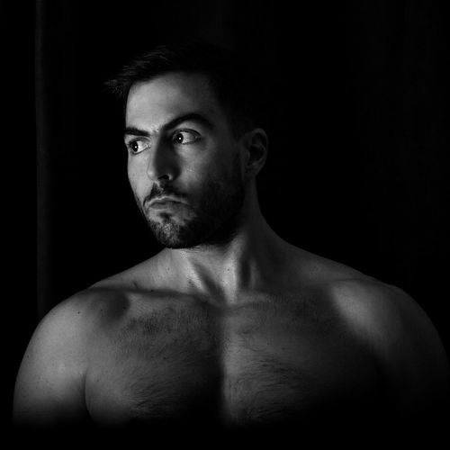 Shirtless Young Man Looking Away Against Black Background